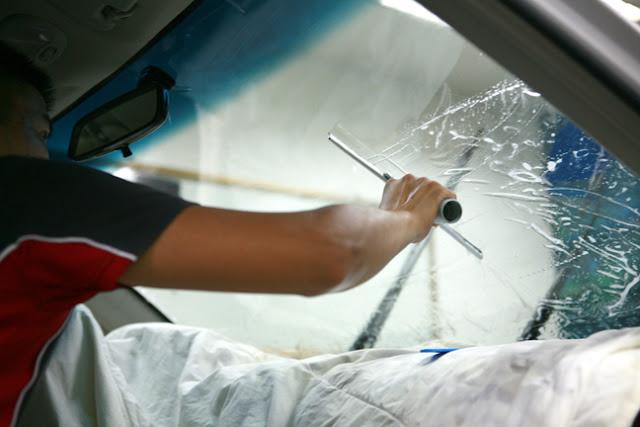Gạt lần 1 bằng tay gạt silicon để loại bỏ xà phòng và nước ra khỏi mặt tiếp xúc giữa tấm phim và kính lái.