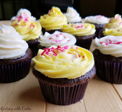 chocolate cupcakes with yellow and white sweetened condensed milk buttercream piped on top and sprinkles