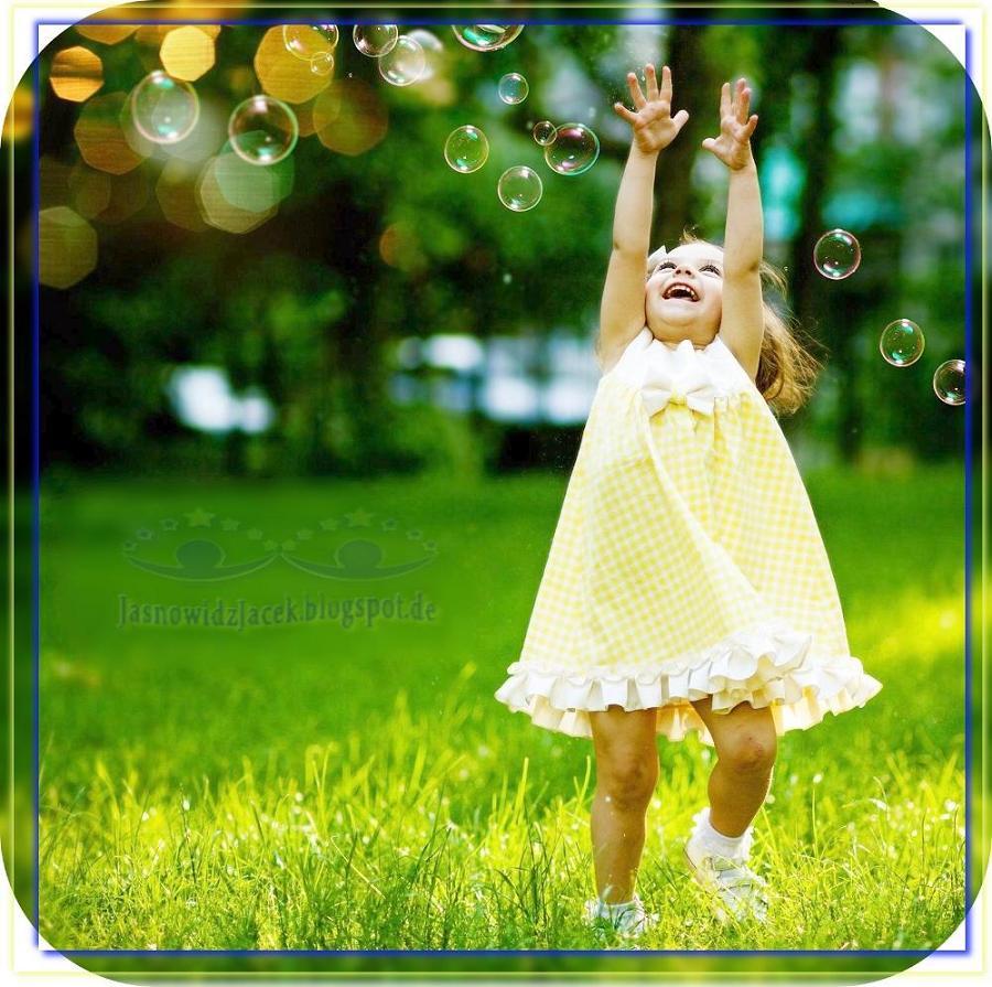 Radość i Szczęście - Dziecko na trawie bawiące się bańkami