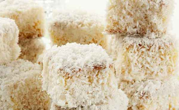 Bolo Gelado de Coco: imagem mostra resultado da receita com pedaço de bolo coberto com coco ralado #PraCegoVer