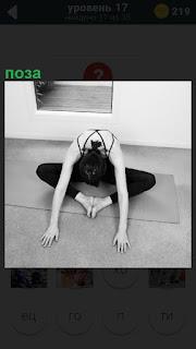 На полу девушка приняла позу йоги, склонив голову и соединив ного пятками
