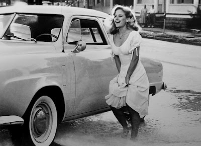 black and white shot of Kelly Preston holding up her skirt and dancing in water from broken fire hydrant