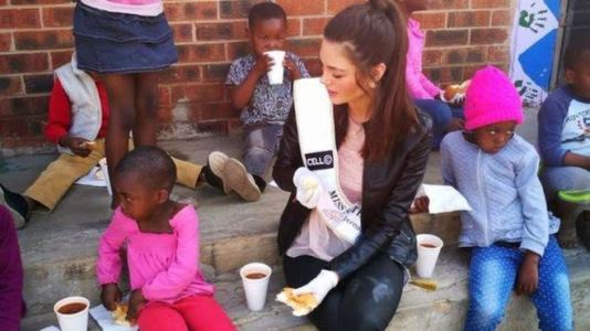 Photos: Miss South Africa accused of racism for wearing gloves while with black children at an orphanage