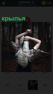 На фоне темного леса стоит женщина, у которой на спине крылья
