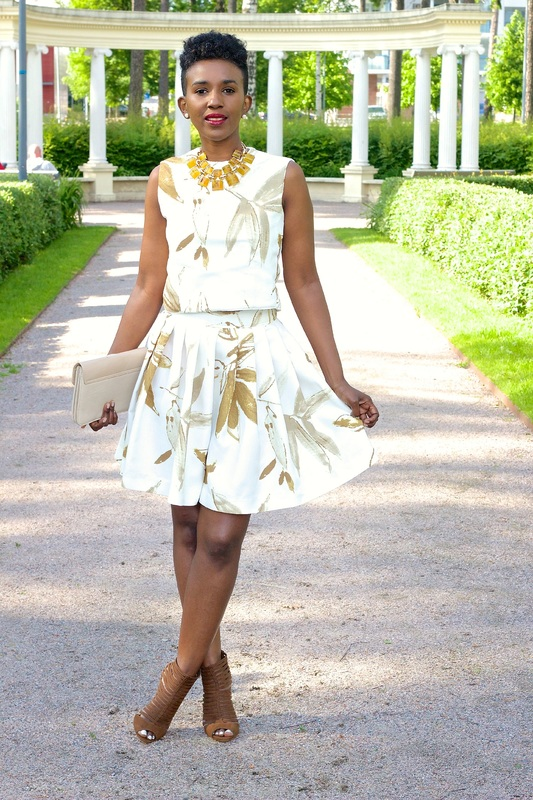 woman wearing a white and golden outfit with a pair of brown heels is curtseying