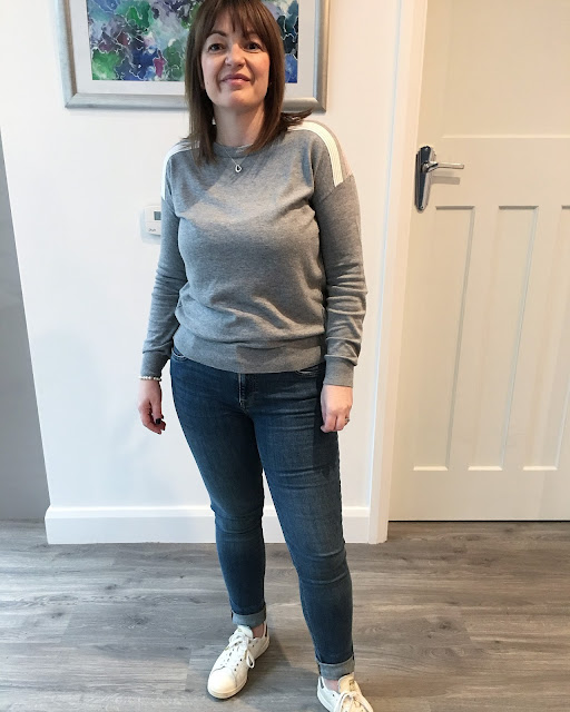 grey jumper and jeans