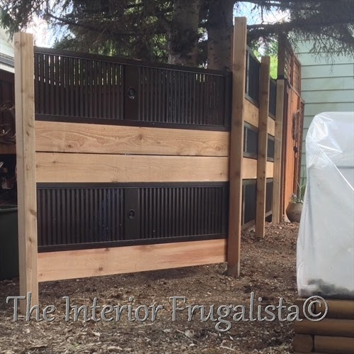 Cedar fence posts between old louvered doors hung horizontally to make a garden screen