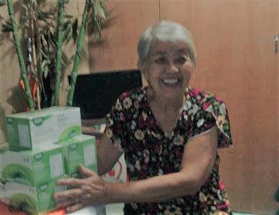 Resurreccion's mother holding boxes of Sante Pure Barley.