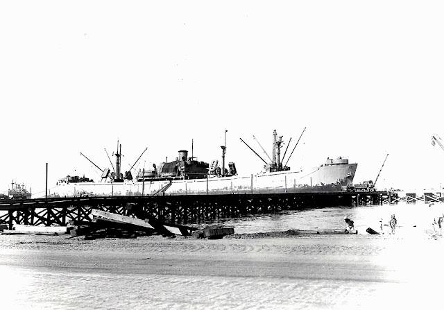 The newly constructed Liberty Berths are adjuncts of the port command at Base R, Batangas, Luzon P.I.  The first ship to dock is anchored there in Batangas Bay.  Taken 29 June 1945.