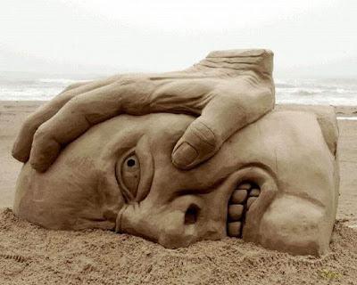 Escultura de arena cara y mano