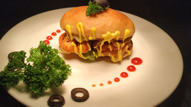 Garnished hot dog sandwich with olive and parsley