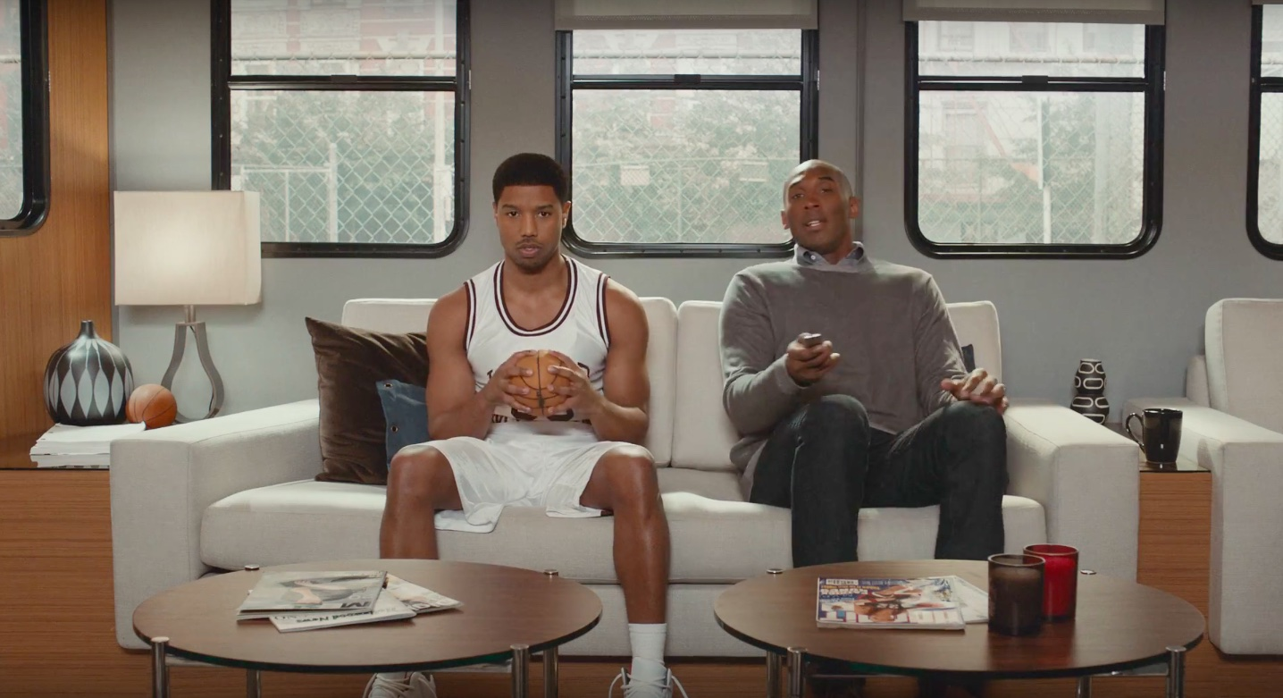 The Two Men Are Sitting On Couch In A Trailer And Jordan Picks Up His Siri Remote To Ask Personal Digital Assistant Open Official NBA App