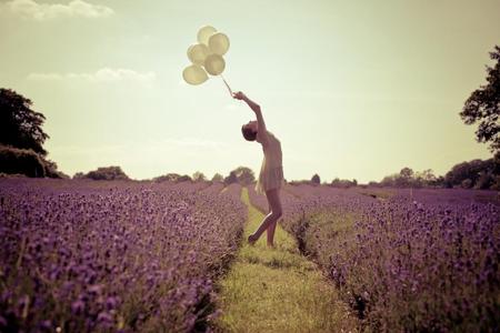 Mujer joven jugando con globos de colores en un camino que divide un campo de lilas.