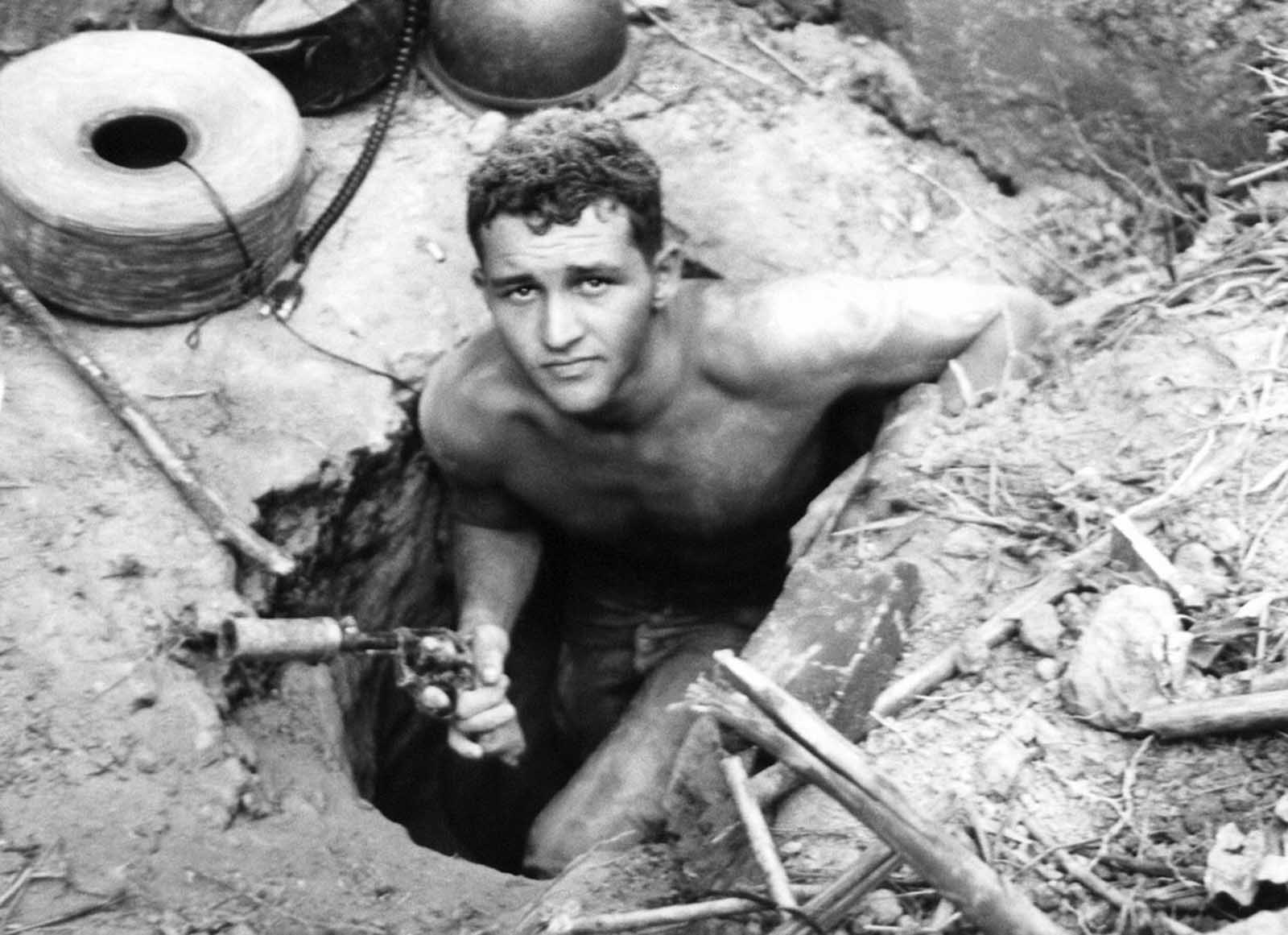 "Sergeant Ronald Payne, 21, of Atlanta, Georgia, emerges from a Viet Cong tunnel holding his silencer-equipped revolver with which he fired at guerrillas fleeing ahead of him underground. Payne and others of the 196th light infantry brigade probed the massive tunnel in Hobo Woods, South Vietnam, on January 21, 1967, and found detailed maps and plans of the enemy. The infantrymen who explored the complex are known as ""Tunnel Rats."" They were called out of the tunnels on January 21, and nauseating gas was pumped in."