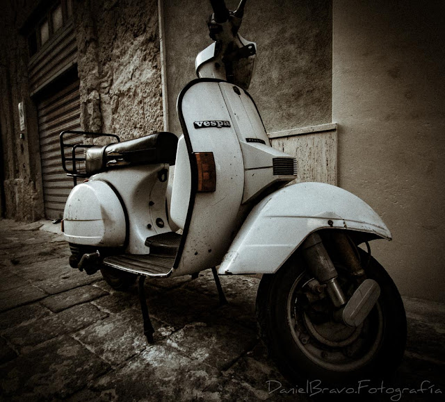 Moto Vespa blanca en una calle de Sicilia