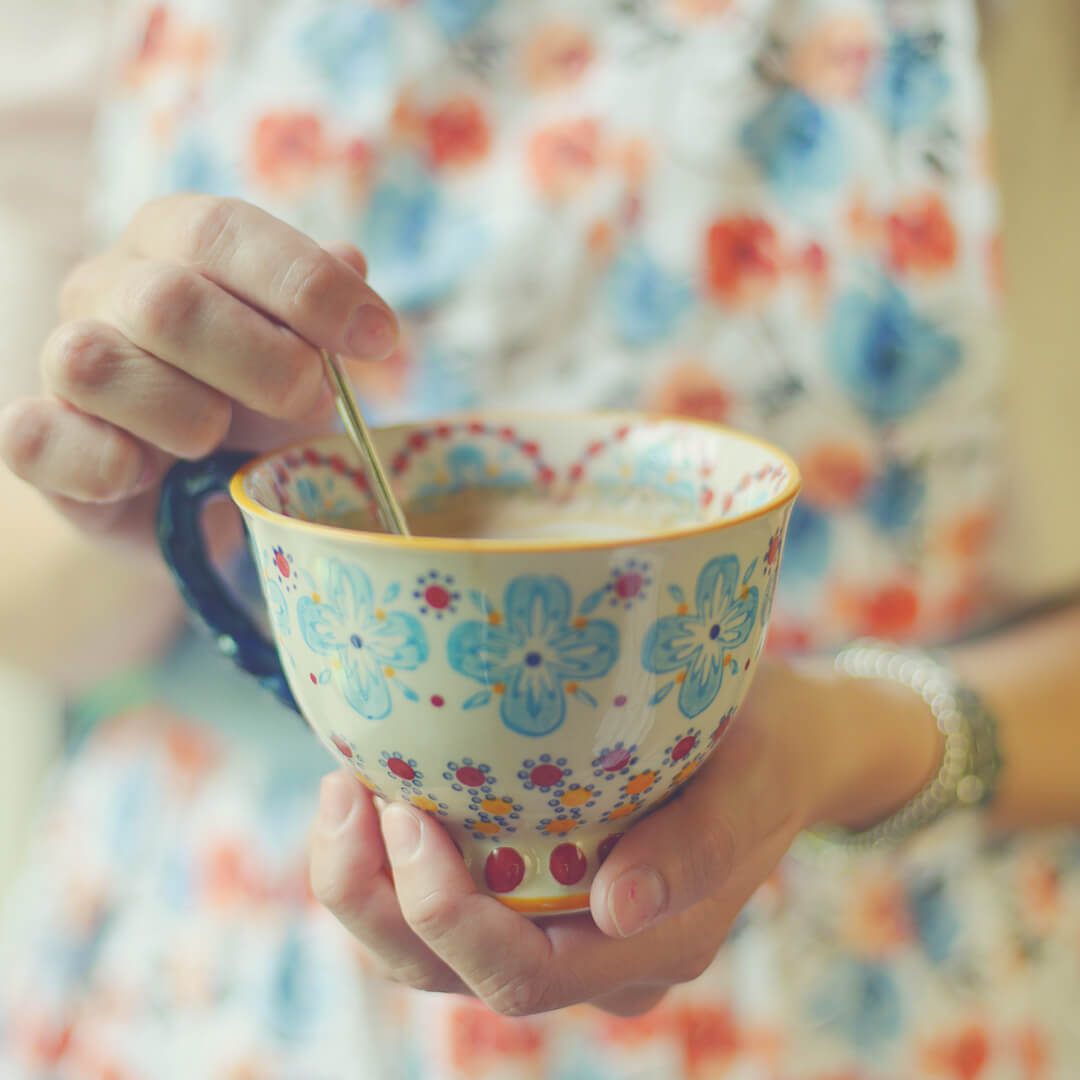 A cup of tea held in the hands of a woman dressed in a flowery dress.
