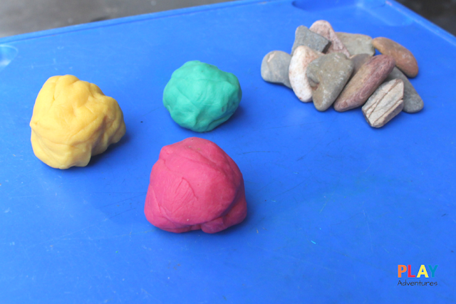 Setting up the activity with balls of playdough and a pile of rocks