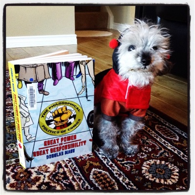 A fuzzy grey poodle, Murchie, sits beside a trade paperback copy of Great Power and Great Responsibility. He sits facing the viewer and wears a black-hooded red costume with antennae on it. The book's cover features a drawing of many peoples' feet surrounding a tiled floor into which a seal reading 'The Philosophical Polics of Comics' is set.