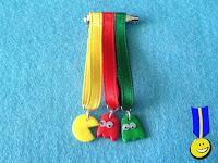 Medalla de tres cintas: amarilla con comecocos amarillo, roja en el centro con fantasma rojo y verde con fantasma verde