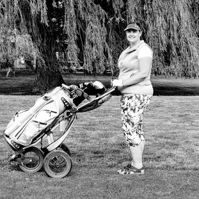 black and white photo of woman and golf bag