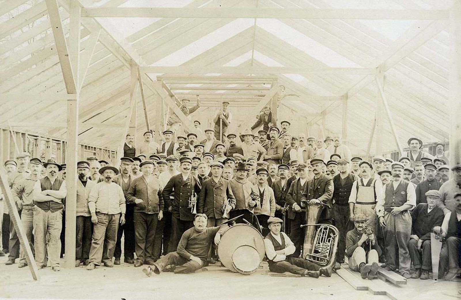 Internees and members of the German Imperial Band pose in a partially-constructed building.