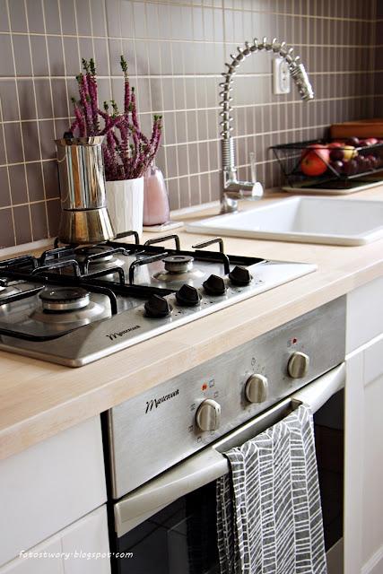 biała kuchnia, ciemne kafle, zlew ceramiczny, bateria, drewniany blat
