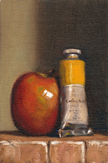 Oil painting of a yellow tube of artists' oil paint beside an apple.