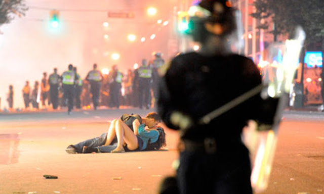 Couple kissing during a riot in Vancouver. Frighten the Horses. marchmatron.com