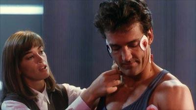 Tina McGee (Amanda Pyes) examinando a Barry Allen (Jonh Wesley Shipp) en The Flash (1990).