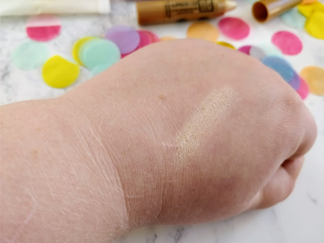 A hand swatch of Glamazon stick, which is a pale gold shimmer