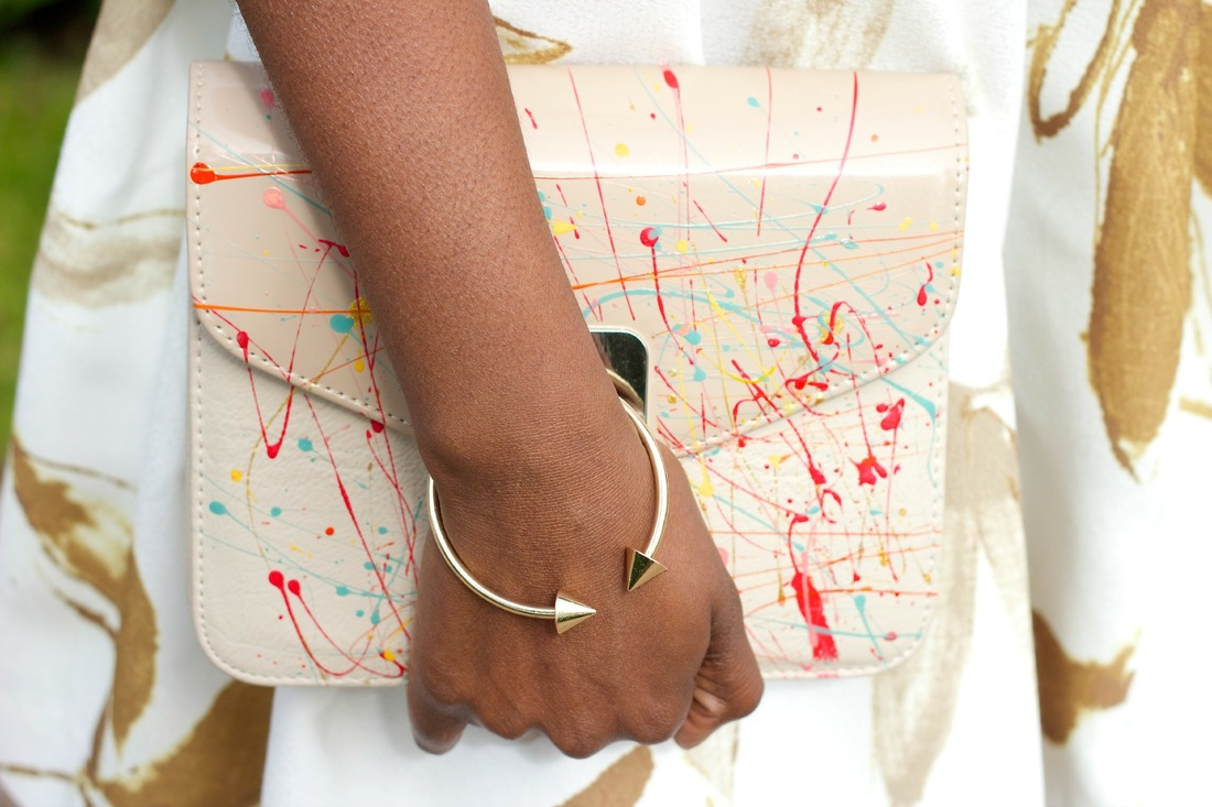 hand with golden bracelet holding a white clutch bag with a detail of splashes of of color