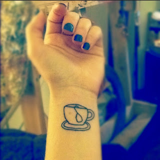brazo de mujer con tatuaje en la muñeca de taza de cafe