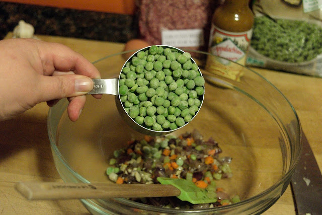 Frozen peas being added to the sauteed vegetables.