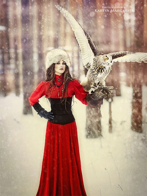 Woman wearing Neo-Victorian clothing (fur hat, underbust corset, red blouse, red skirt, gloves) in the snow with an owl perched on her glove