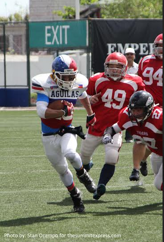 Running Back Johnny Babaran of Pilipinas Aguilas passes through three Tigers for a Touchdown