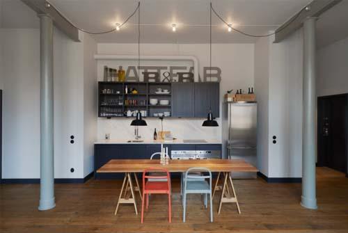 Cucina con pensili scuri e tavolo in rovere - esempi stile industriale