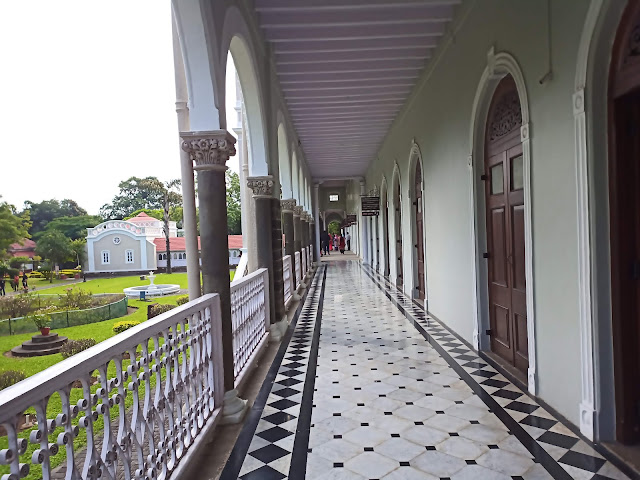 View of tiled balcony of Aga Khan Palace with arched doors to right and railing to left, and garden beyond