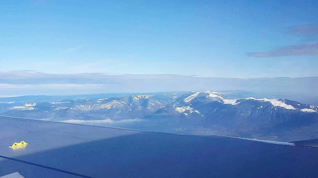 A view of a snow covered mountain from a plane window