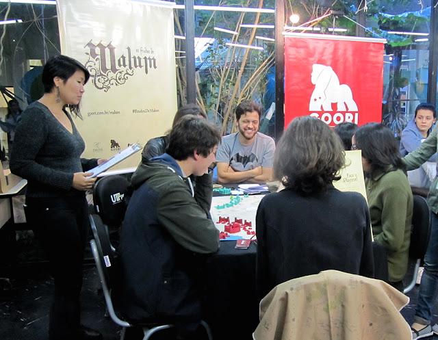 Na foto aparece a mesa com quatro pessoas e mais duas pessoas membros da equipe Goori. Ao fundo, dois banner .