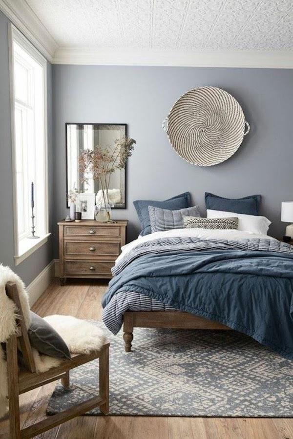 Pared de cabecero pintada en azul con objeto de fibra natural como decoración
