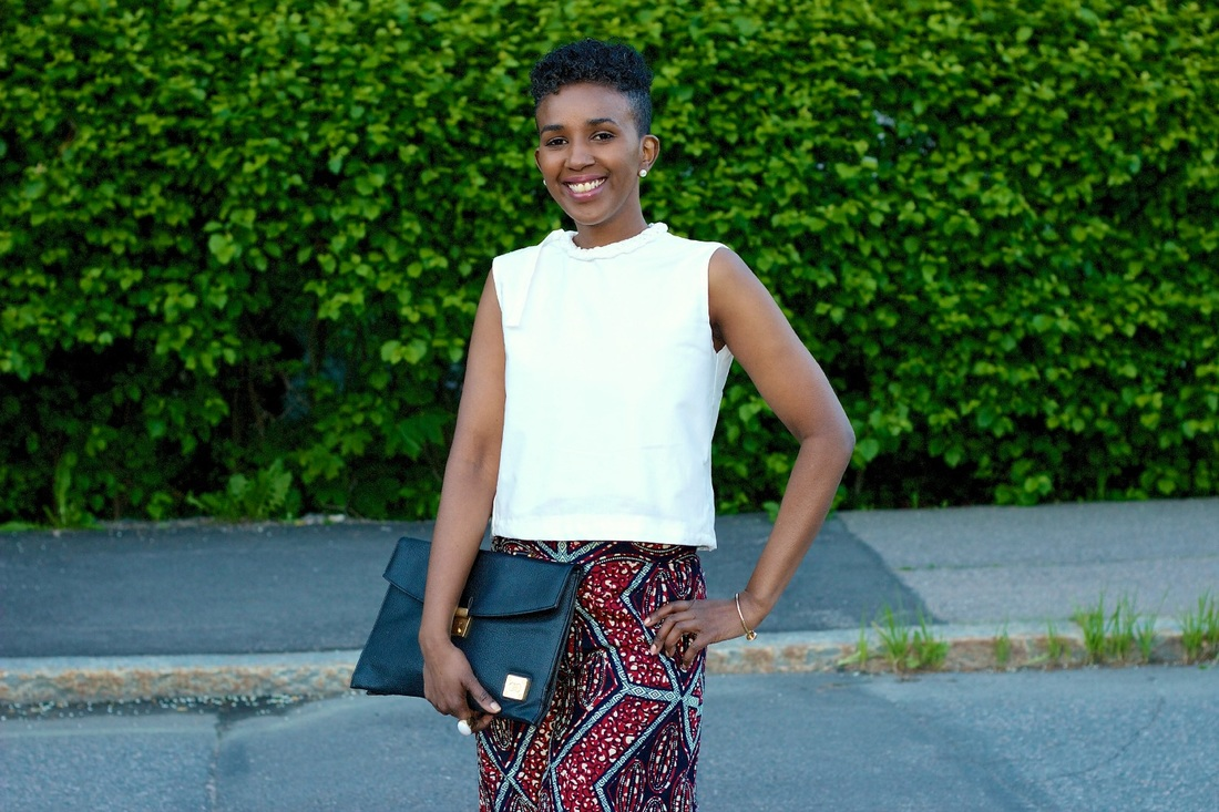 smiling woman wearing white top, african print pants with clutch bag in hand is standing infront of a green hedge