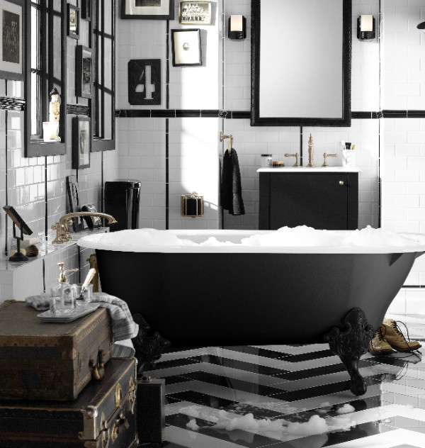 Bold eclectic black and white bathroom with black clawfoot tub and gallery wall of art