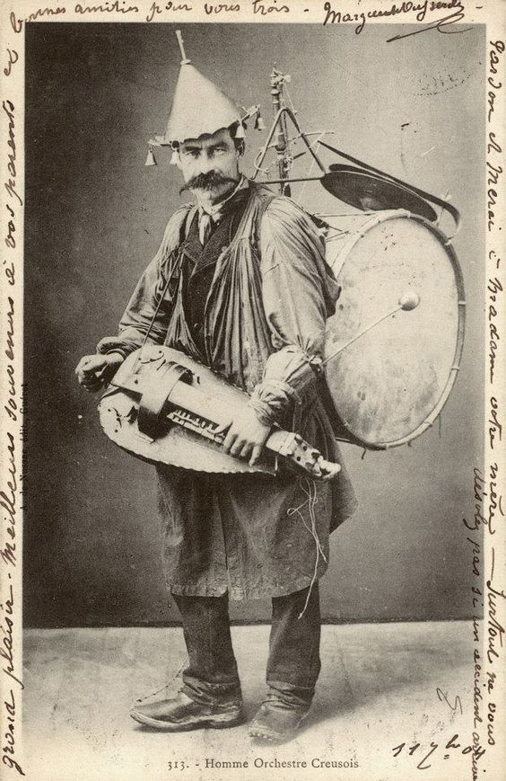 Vintage photo. One man band. Dapper gent covered in musical accoutrements jingle hat and a hand cranked Hudy-Gurdy. Jingles and other stories of The American Dream. marchmaton.com