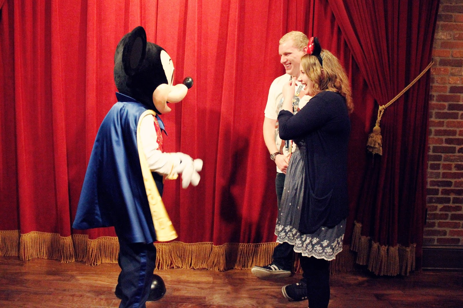 Couple meeting Mickey Mouse in his theater.