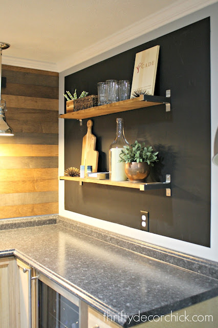 Basement kitchenette with chalkboard wall and shelves