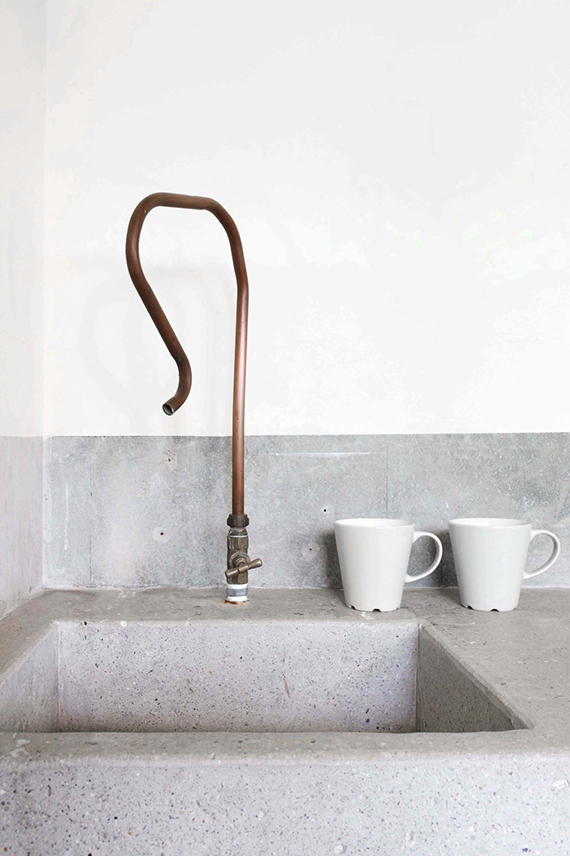Concrete sink and pipe faucet. Photo by Marjon Hoogervorst