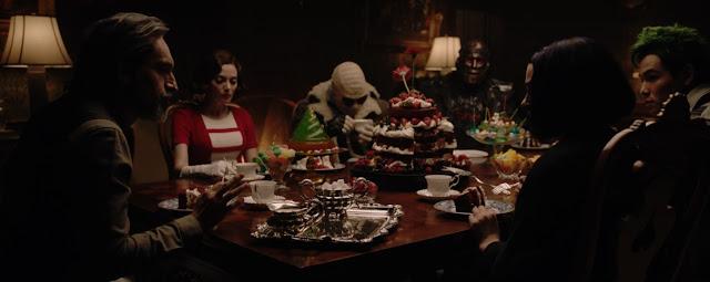 bizcocho de chocolate, con nata y fresas para montar una enorma tarta naked , la doom patrol rodea una gran mesa de madera, vemos también montañas de gelatina, y dulces de todo tipo