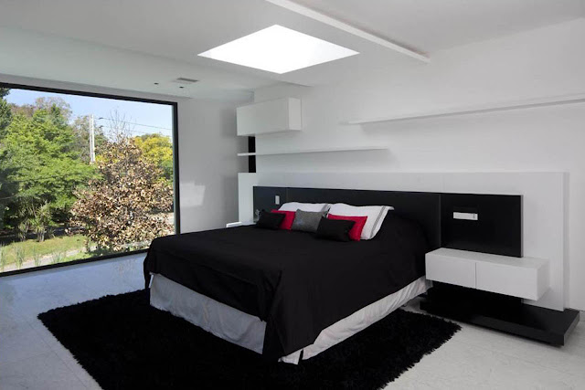 amazing black and white bedroom with modern high bed and big black fur rug