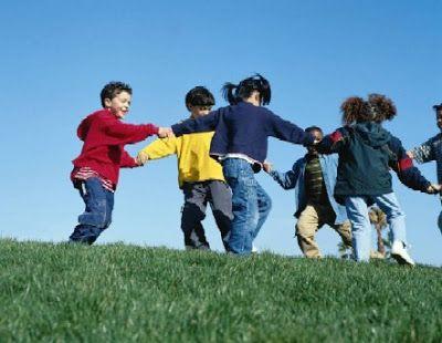 Convivencia. Niños haciendo una ronda sobre el césped