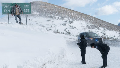 """A dead body hangs from a road sign as Emmy Rossum and John Doman investigate in the new film """"Cold Pursuit"""""""